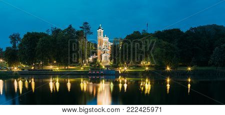 Mir, Belarus. Panorama Of Evening Lake Of Chapel And Burial Vault Of Svyatopolk-Mirsky Family In Bright Illumination. Part Of Architectural Ensemble Of Mir Castle Complex Under Blue Sky.