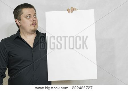 A man is holding an empty scoreboard or white square of paper. The white square is empty. copyspace