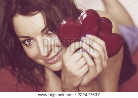Beautiful woman with two red hearts. Valentine's Day. Nostalgic filter.