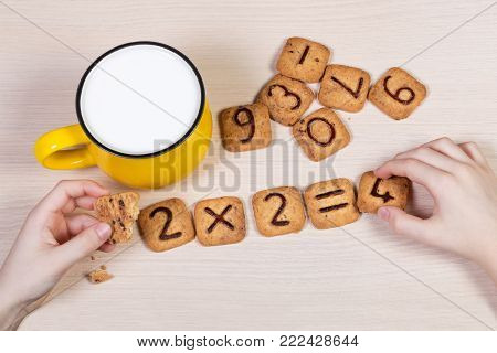 Healthy breakfast for a school children. Milk in bright yellow cup and funny cookies with numbers. Child's hands doing sums using biscuits. Idea of easy arithmetics during eating. Top view.