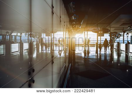 Silhouettes of several moving off people inside of interior of modern airport terminal or railroad depot station, or shopping mall; with white reflective glass wall, cafe fencing and windows behind
