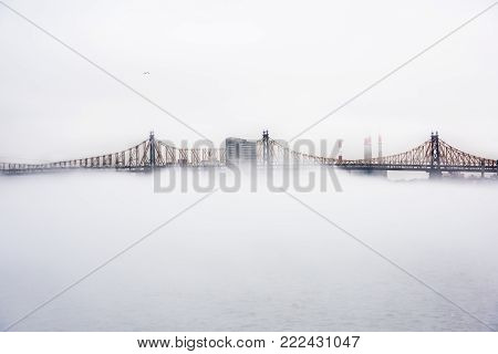 A dense fog covered New York City during the winter's day on January of 2018. View of Ed Koch Queensboro Bridge.