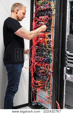 Side view of mid adult male IT engineer checking with network cables connected to servers in datacenter