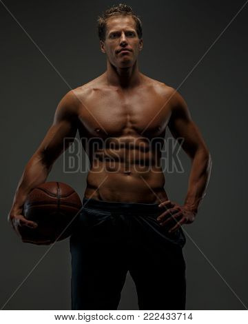 Awesome muscular femail in black shorts with basket ball in a hand. Grey background.