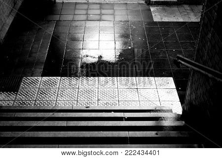 The dark steps of a station tunnel with puddles and damp walls.