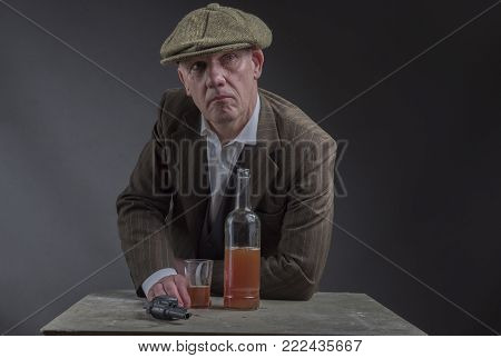 Mature Victorian gangster drinking whisky and leaning against a table with a hand gun