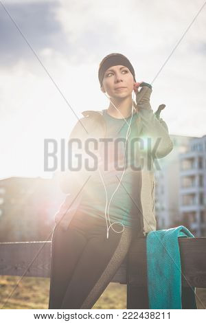 Portrait of young woman ready for outdoor workout listening to music through in-ear headphones connected to the mobile phone