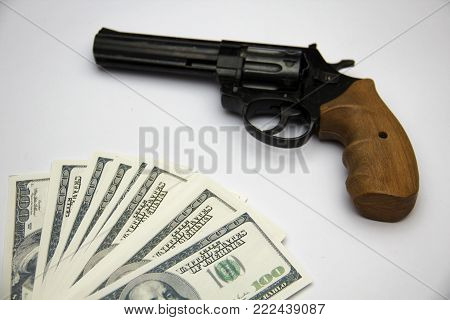 A huge revolver on a white background with hundred-dollar bills