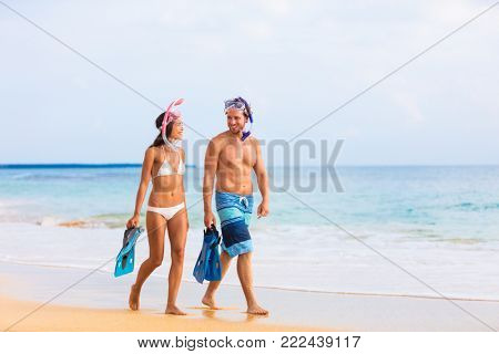 Snorkel couple walking holding hands on beach vacation after swim at sunset. Honeymoon holiday people relaxing on summer holidays.