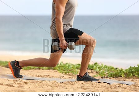 Lunge leg workout with dumbbells weights. Fitness man doing lunges training legs on beach summer outdoors with weight.