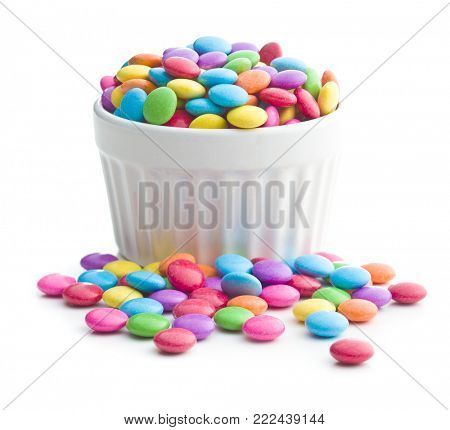 Colorful chocolate candies in bowl isolated on white background.