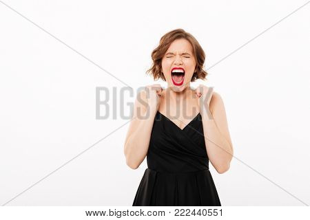 Portrait of an angry girl dressed in black dress screaming isolated over white background