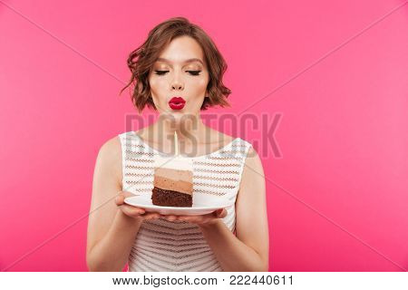Portrait of a pretty girl holding plate with a piece of birthday cake and blowing a candle isolated over pink background
