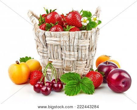 Berry in wicker basket still life with fruits and green leaves, isolated on white background.