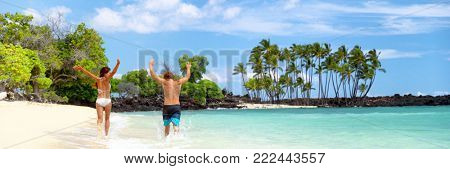 Summer fun beach couple running of joy banner with arms up in success on travel holidays. Happy people on tropical landscape background panoramic copy space.