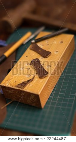 Leather craft. leather parts being created on a cutting board. Leather craft tools around the piece.