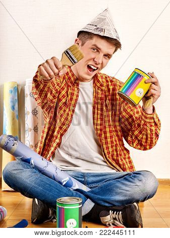 Repair home man holding paint roller for wallpaper. Happy mad male in newspaper cap renovation apartment and joy discounts for building materials for students. Paint bank and paint brush in hand.