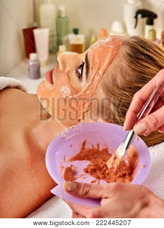 Collagen face mask. Facial skin treatment. Woman receiving cosmetic procedure in beauty salon. Bottle with moisturizing cream on background. Mask against black dots. Facelift.