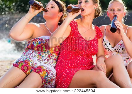 Friends drinking beer together at river beach
