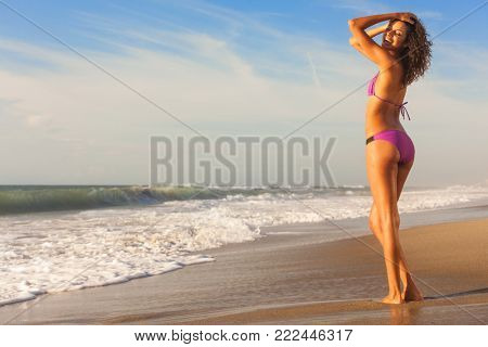 Beautiful young woman in bikini with sun tan in sunshine on a deserted tropical beach with blue sky