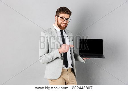 Portrait of a smiling businessman dressed in suit and eyeglasses pointing finger at blank screen laptop computer isolated over gray background