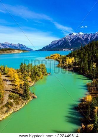 Warm September in the mountains of Canada. Exquisite Abraham Reservoir Lake with turquoise water. On coast of the lake autumn multi-color woods. Concept of ecological and active tourism