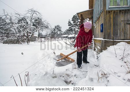 Elderly woman cleans the snow near home.