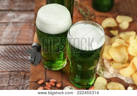 Glasses of green beer and snacks on wooden table. Saint Patrick's day celebration