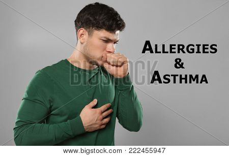 Young man suffering from cough as symptom of asthma or allergies on color background