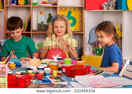 Small students with teacher finger painting in art school class. Teacher cheers children in kindergarten. Newcomer in children's team. Craft drawing education develops creative abilities of children.