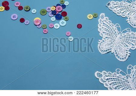 Arts and crafts background image of colourful buttons and lace butterflies, taken with copy space