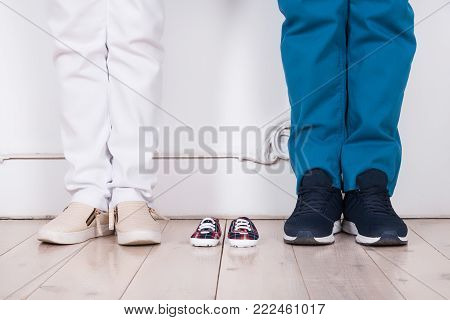 Feet of a married couple in anticipation of a baby on the background