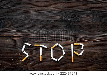 Stop smoking. Word stop lined cigarettes on dark wooden background top view.