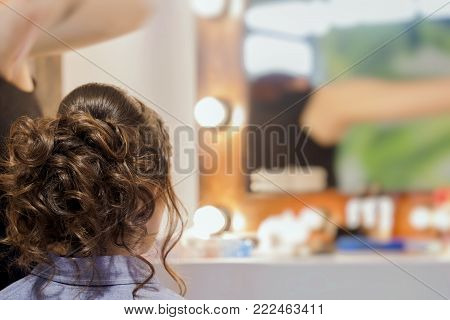 Unrecognizable girl back to us, young woman in  mirror at hairdresser  making hairstyle, styling  from  long hair in hair salon. Hands of  master, hairdresser are  partially visible. Selective focus