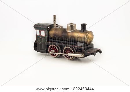 Isolated model of old train locomotive. Antique toy hobby collection. Single isolated locomotive on the white background.