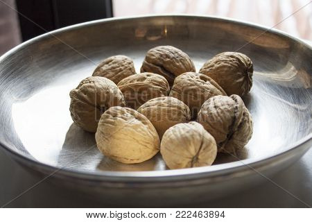 Some walnuts on metal plate on the table