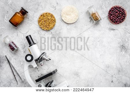 Food safety. Wheat, rice and red beans near microscope on grey background top view.