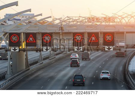 High-speed highway with traffic cars and speed limit signs and a slippery road warning