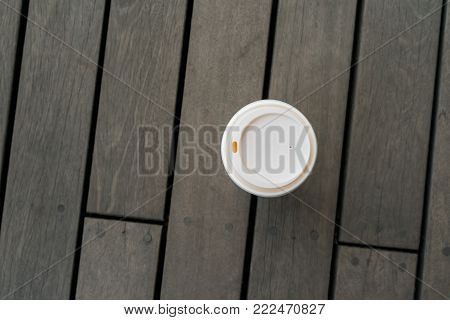 Top view of single hot latte on vintage wooden floor at relaxing balcony. Paper coffee cup with plastic lid.