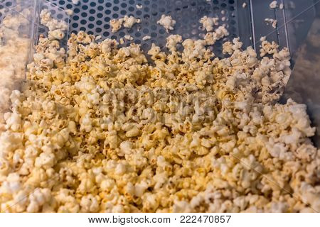 A closed up look through glass cabinet of salted butter popcorn in incubator machine at movie counter bar.