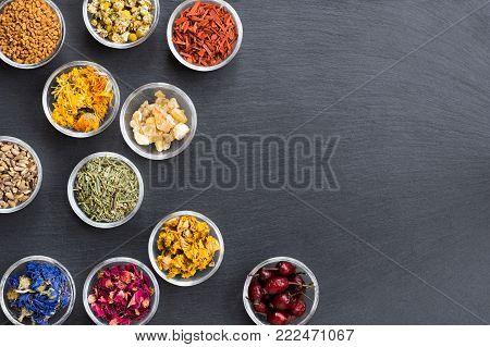 Mix of herbs on dark background with copy space: fenugreek, calendula, sandalwood, frankincense resin, horsetail, milk thistle, cornflower, rose petals, mullein, dried rose hips, chamomile, oak bark