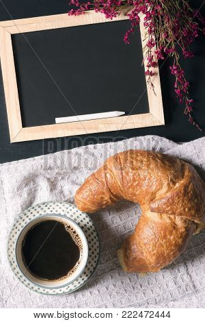 Blank blackboard and flowers with breakfast - Breakfast arrangement with a cup of coffee, a croissant on a vintage kitchen towel and a chalkboard decorated with pink flowers, on a  black table.