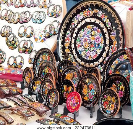 Patzcuaro, Michoacan, Mexico - winter 2017: Display of lacas perfiladas arts and crafts stand in the open-air art market, including colorful decorated plates, earrings and hair brooches painted by hand.