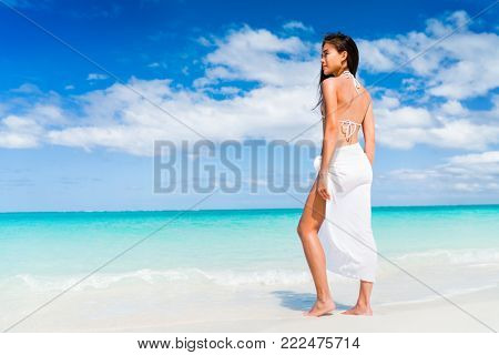 Elegant Asian woman in white beachwear bikini and fashion sarong standing on beach. Luxury travel vacation. Swimsuit swimwear model girl on summer holiday in the Caribbean.