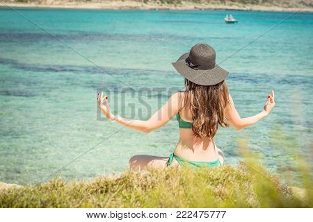 Young Woman In Green Swimsuit And Black Hat Practices Yoga On The Beach Of The Mediterranean Sea. Qi
