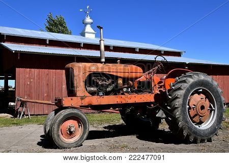 DALTON, MINNESOTA, Sept 8, 2017: An old WD Allis Chalmers tractor with a wood shed in the background is displayed at the annual Dalton Threshing Bee farm show in Dalton held each 2nd full weekend in September where 1000`s attend.