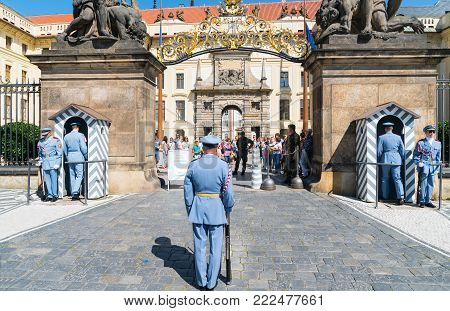 PRAGUE - CZECH REPUBLIC - AUGUST 29 2017; changing of guard ceremony at Prague Castle gates, new guards enter sentry boxes while old wait and toutrists crowd inside gates.