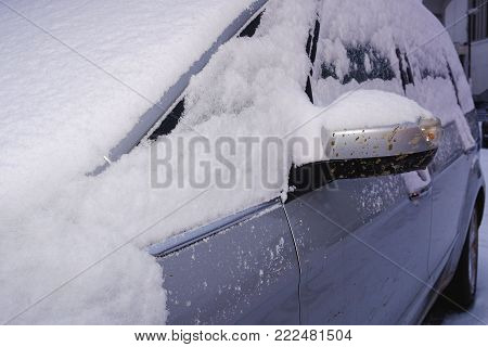 Closeup of a car covered with snow. Silver car in winter