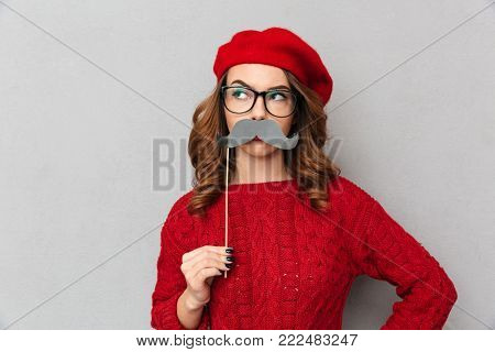 Portrait of a funny woman dressed in red sweater and eyeglasses holding fake mustaches and looking away isolated over gray wall background