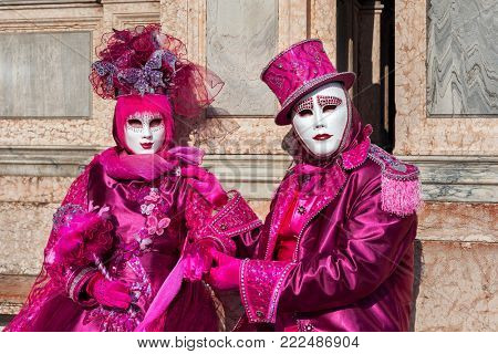 VENICE, ITALY - FEBRUARY 18, 2017: Unidentified participants wear vintage colorful costumes and white masks during famous traditional Carnival taking place each year on february in Venice, Italy.